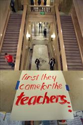 A sign supporting teachers is taped to the railing above a stairway in the state capitol February 23, 2011 in Madison, Wisconsin.