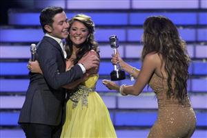 Winner Scotty McCreery hugs finalist Lauren Alaina as Jennifer Lopez hand him his trophy at the American Idol finale.