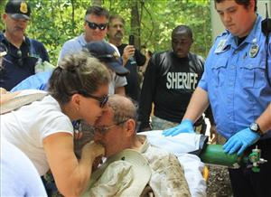 Francisco Piedrahita's wife Claudia, left, gives him a kiss as he is transferred to a waiting ambulance as rescue and search team members wait in the background.