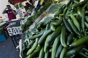 A street vendor stands next to cucumbers on sale in Berlin on Monday.