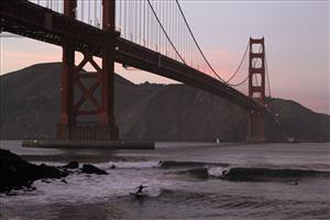 Surfers catch waves late in the day at Fort Point beneath the Golden Gate Bridge in San Francisco, Wednesday, Jan. 19, 2011.
