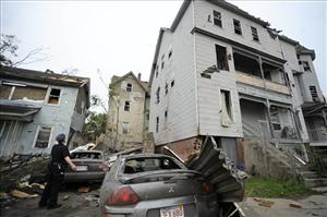 A police officer checks on people in a house after a tornado struck Springfield, Conn., Wednesday, June 1, 2011.