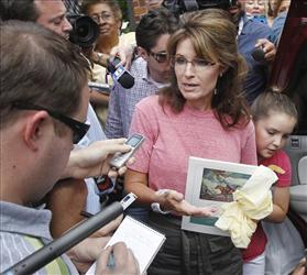 In this June 2, 2011, file photo former Alaska Gov. Sarah Palin, holding a booklet depicting Paul Revere, speaks briefly with the media as she tours Boston's North End neighborhood.