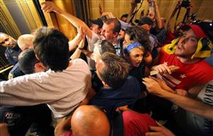Police, left, with a protester in custody, push back as other protesters try to prevent the doors of a ground floor elevator from closing at the Capitol in Madison, Wis. on Monday, June 6, 2011.