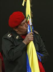 Hugo Chavez kisses a Venezuelan flag after greeting supporters at  Miraflores presidential palace in Caracas.