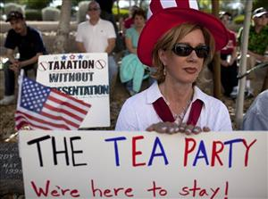 In this file photo taken April 15, 2011, in Las Vegas, Diana Orrock of Las Vegas listens to speakers during a tea party rally to support Nevada Governor Brian Sandoval's promise not to raise taxes.