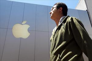 A pedestrian walks by an Apple Store on July 19, 2011 in San Francisco, California. With $76 billion in cash, investors are calling on Apple Inc. to use that money.