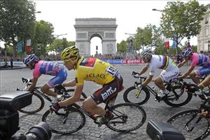 Cadel Evans of Australia, wearing the overall leader's yellow jersey, and Thor Hushovd of Norway, wearing the rainbow jersey, second right, pass the Arc de Triomphe, Sunday July 24, 2011.