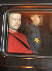 Bomb and terror suspect Anders Behring Breivik (red top) leaves the courthouse in a police car  in Oslo on July 25, 2011, after the hearing to decide his further detention.
