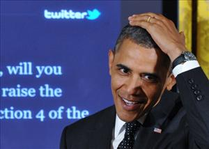 President Barack Obama speaks in front of a screen showing his tweet at the start of a 'Twitter Town Hall' July 6, 2011 in the East Room.