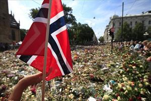 A woman touches a Norwegian flag as people gather around thousands of flowers and tributes laid outside the Oslo Cathedral in Oslo in July.