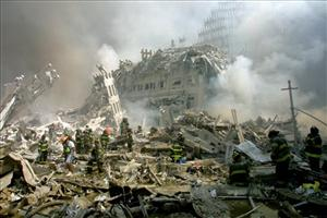 In this Tuesday, Sept. 11, 2001 file photo, firefighters walk through the rubble of the collapsed World Trade Center buildings after terrorists crashed two airliners into the towers.