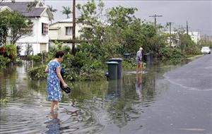 Residents leave their homes after storms spawned by Cyclone Larry caused widespread flooding around Innisfail, Australia, March 2006.
