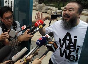 Activist artist Ai Weiwei gestures while speaking to journalists gathered outside his home in Beijing, China, Thursday, June 23, 2011. Ai, the most high-profile target of a sweeping crackdown on activists in China, has returned home late Wednesday after nearly three months in detention. The official Xinhua News Agency said...