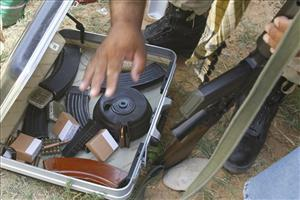 A rebel military chief checks a case during a raid to find illegal weapons near Tripoli.