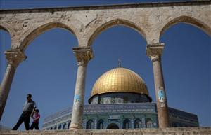 A Palestinian man and child walk past the Dome of the Rock Mosque in the Al Aqsa Mosque compound yesterday.