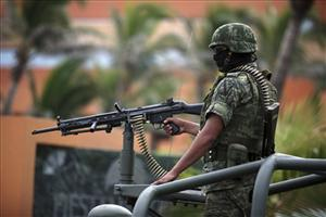 A Mexican army soldier mans a gun on top of a vehicle while guarding the perimeter around the site of a state prosecutors convention in the Gulf port city of Veracruz, Mexico, Thursday Sept. 22, 2011.