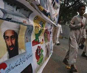 A Pakistani boy walks past a poster of al-Qaida's slain leader Osama Bin Laden fixed on a grill by supporters of a Pakistani religious party Jamaat-e-Islami in Lahore, Pakistan.