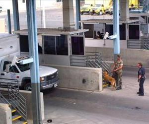 A US Customs Inspector and a US marine check in vehicles at the Bridge of Americas port of entry cargo facility March 28, 2002 in El Paso, TX.