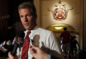 In this Aug. 5, 2011 photo US Sen. Scott Brown, R-Mass., faces reporters at a hotel in Boston.