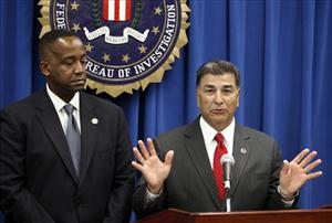 U.S. Attorney Andre Birotte Jr., left, and an FBI official announce the arrest of Christopher Chaney, 35, of Jacksonville, Fla.