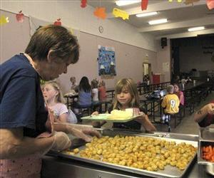 In this Sept. 30, 2010 photo, school cook Mavis McDowell, left, serves up tater tots to second-grader Madison Nunley at Naches Valley Primary School in Gleed, Wash.