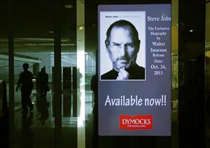 People walk past a screen showing the cover of  the book Steve Jobs, by Walter Isaacson at a book shop in Hong Kong Monday, Oct. 24, 2011.