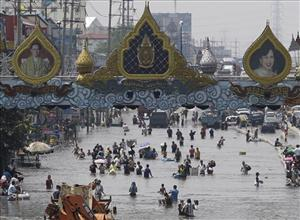 Residents wade through floodwaters in the Rangsit district on the outskirts of Bangkok.