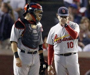 St. Louis Cardinals' Yadier Molina, left and Tony La Russa wait for relief pitcher Jason Motte to enter the game.