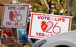 Christi Chandler, left, and Stacy Hawsey, supporters of the personhood amendment, wave signs at drivers in Madison, Miss.
