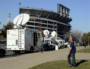 In this Monday, Nov. 7, 2011 file photo, satellite trucks begin to fill a parking lot near Beaver Stadium in State College, Pa.