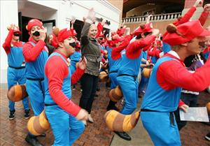 "Consumers join in as a group of Marios take over Westfield Horton Plaza in San Diego, Calif., on Friday, Nov. 4, 2011, and perform the ""Tanooki Trot."""