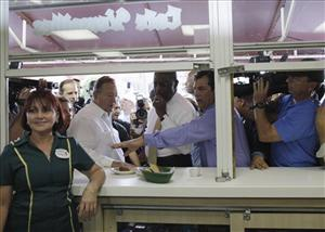Herman Cain samples Cuban pastry while campaigning at the Versailles Restaurant in Little Havana yesterday.