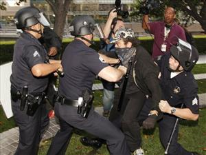 Los Angeles police officers struggle to arrest an unidentified police provocateur in Los Angeles, Thursday, Nov. 17, 2011.