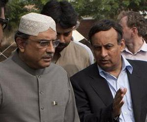 In this 2010 photo, Hussain Haqqani, right, talks with Pakistan President Asif Ali Zardari in Multan, Pakistan.