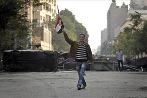 An Egyptian protestor walks with his national flag in front of a road barricade near the Egyptian Interior Ministry in downtown Cairo, Egypt, yesterday.