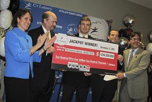 Wealth managers Tim Davidson, second left, Greg Skidmore, center, and Brandon Lacoff, second right, pose Monday, Nov. 28. 2011 with a ceremonial check after claiming a $254 million Powerball jackpot.