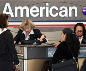 Passengers check in at an American Airlines ticketing counter at Dallas Fort Worth Airport Tuesday, Nov. 29, 2011, in Dallas.