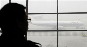 A traveller looks out at an airplane shouded in smog. Beijing authorities cancelled hundreds of flights and shut highways as thick smog descended on the Chinese capital.