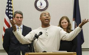 Thomas Haynesworth, who spent 27 years behind bars, center, gestures during a press conference in Richmond, Va., Tuesday, Dec. 6, 2011.
