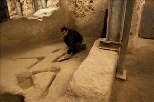 Israeli archeologist Eli Shukron sweeps marks carved in the bedrock in an archeological excavation.