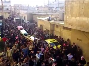 In this image from amateur video made available by the Ugarit News group on Wednesday, Dec. 7, 2011, the coffins of three protesters are carried during a march in Homs, Syria.