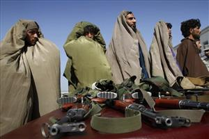 Taliban militants arrested by the Afghan Border Police stand over their guns while they are presented to the media at the Afghan Border Police headquarters in Jalalabad.