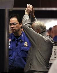 A TSA officer looks on as a passenger holds up his arms while going through a full-body scan at a security check-point at Seattle-Tacoma International Airport in Seattle.