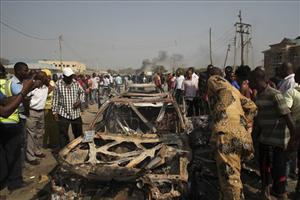 Onlookers stand by a destroyed car at the site of a bomb blast at St. Theresa Catholic Church in Madalla, Nigeria, Sunday, Dec. 25, 2011.