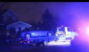 One of the cars in which bodies were found is towed away from the scene on the east side of Detroit.