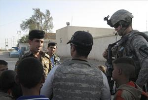 In this Monday, Aug. 29, 2011 photo, a U.S. Army captain and a translator talk with an Iraqi Army soldier while delivering toys and water to residents in the village of Bani Hashem, Iraq.