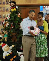 President Obama and the First Lady (in a $1,000 skirt, according to fashionistas) pose with a baby while greeting service members and their families on Christmas Day.