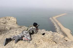 A member of the Iranian military takes position in a drill on the shore of the sea of Oman, on Friday, Dec. 30, 2011.