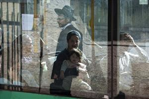 An Ultra Orthodox Jewish man is reflected in a bus window in Jerusalem.